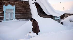 Мужчина расчищает дорожку от снега в деревне Бобровка, 25 января 2017 года Алексей Мальгавко/РИА Новости